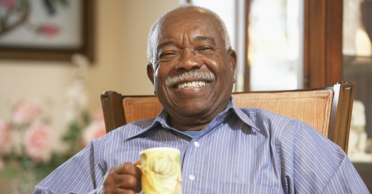 Older man smiling and drtinking coffee