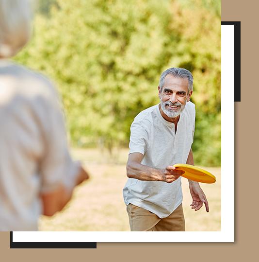 A senior man throwing a Frisbee