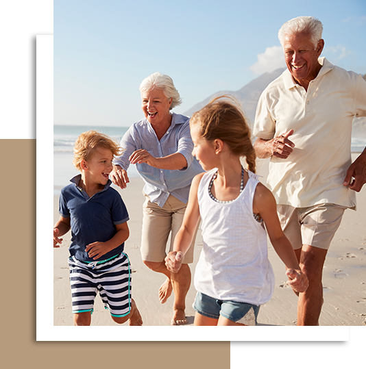 Grandparents spending time with their grandkids on the beach.